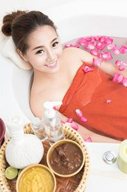 stock photo of beauty parlour  - Beautiful female in bath with rose petal - JPG