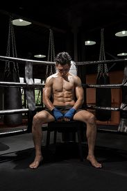 stock photo of boxers  - Portrait of a young boxer sitting on his corner of the ring - JPG