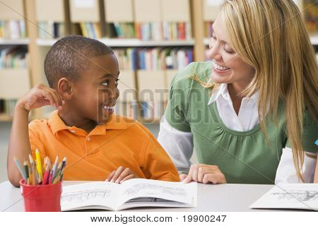 Student in class reading with teacher