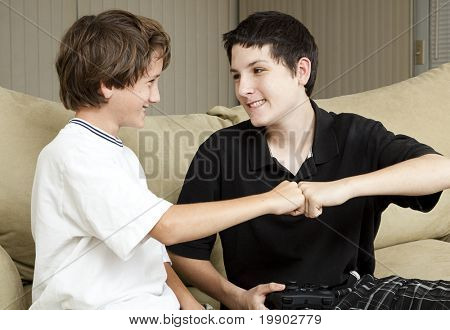 Teen and his younger brother giving each other an affectionate fist bump.