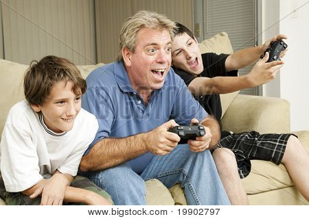 Uncle and his two nephews playing video games together.  Could also be father and sons.