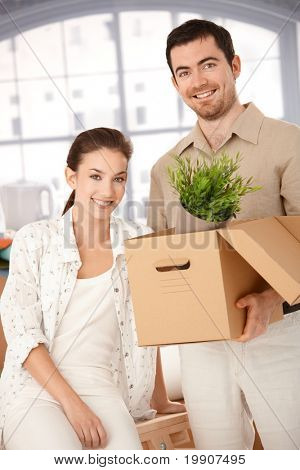 Happy young couple moving to new house, unpacking boxes, smiling.?