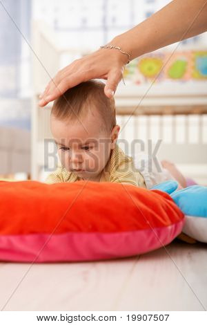 Baby on playmat concentrating, mother holding hand to protect infant.?