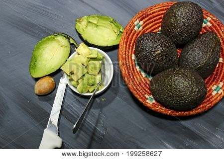 Chopped Avocado in a bowl and in a basket on wooden background