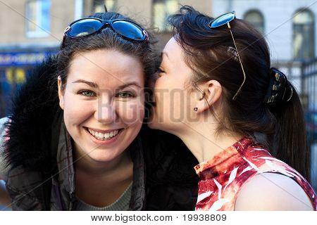 Junge schöne Frau flüstert etwas Freundin ihr ins Ohr