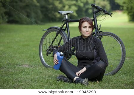 Woman With Bike Resting On Ground