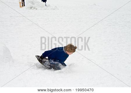 children are sledding down the hill in snow white winter
