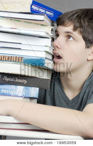 Teen abrumado mira para arriba en la pila de libros de texto