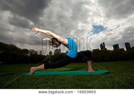 Young Pretty Woman In Blue Top Doing Yoga And Having Fun In Central Park