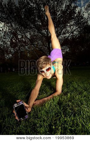 Young Pretty Woman Stretching With Cell Phone In Central Park