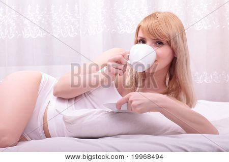 Cute Woman Drinking A Coffee Lying On Her Bed