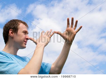 The young man plays about and wriggles against the blue sky