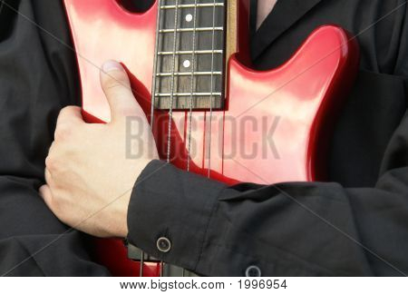 Man'S Hand Embracing A Red Bass Guitar