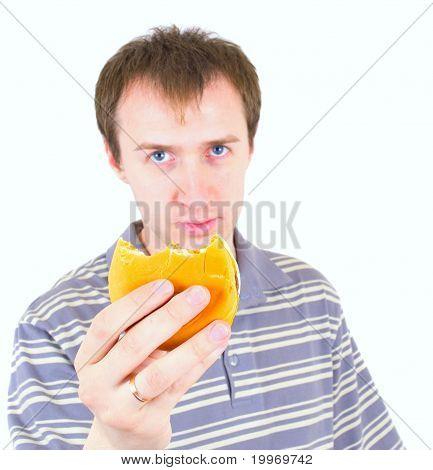 The young man eats a hamburger. Focus on hamburger.