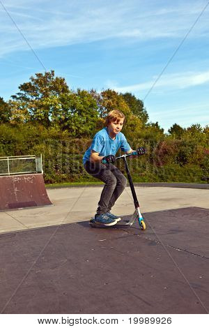 young boy jumping with his scooter at the skate park