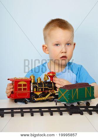 Niño jugando con una locomotora de juguete