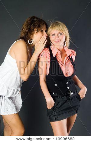 Chica susurrando en el oído de un amigo