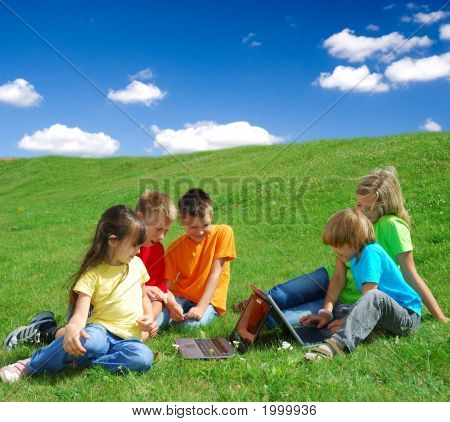Kids In A Meadow With Laptops