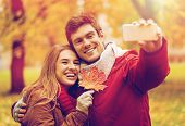 love, technology, relationship, family and people concept - smiling couple with maple leaf taking se poster