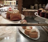 Gourmet Cupcake Display In Elegant Bakery