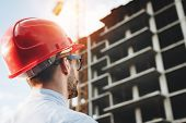 Young Engineer In Red Helmet Inspects Construction Of Building. Bearded Businessman On Background Of poster
