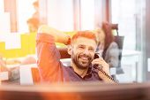 Smiling mid adult businessman talking on phone in office poster