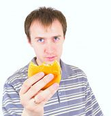 The young man eats a hamburger. Focus on hamburger.