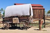 foto of covered wagon  - View of an old covered wagon and a red roofed barn beyond - JPG