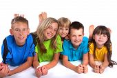 pic of happy kids  - A group of smiling kids pose together while lying belly - JPG