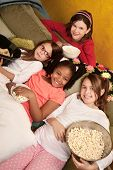 foto of foursome  - Little girls at a sleepover eat popcorn and tortilla chips - JPG