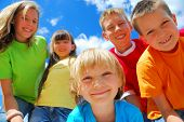 picture of happy kids  - A group of five happy kids with a blue sky behind them