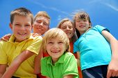 image of happy kids  - A view looking upwards at five happy smiling kids with blue sky and wispy white clouds in the background - JPG