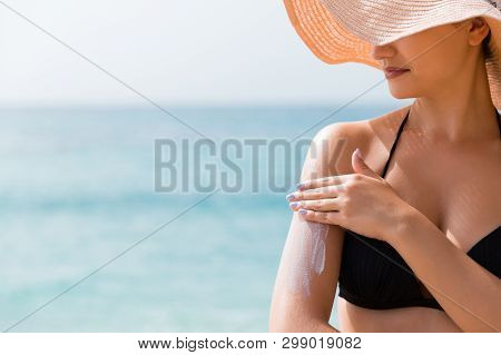 poster of Sunscreen Sunblock. Woman In A Hat Putting Solar Cream On Shoulder Outdoors Under Sunshine On Beauti