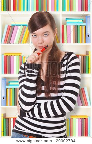 Student girl stands next to the bookshelf