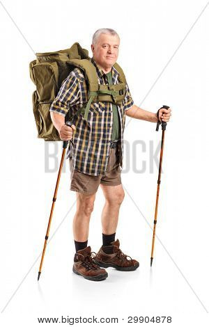 Full length portrait of a smiling mature with backpack holding hiking poles posing isolated on white background