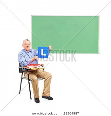 A senior man sitting on a school chair and green school board isolated on white background