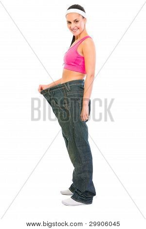 Slim Girl Pulling Oversize Jeans. Weight Loss Concept