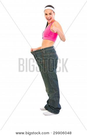 Slim Girl Pulling Oversize Jeans And Showing Thumbs Up. Weight L