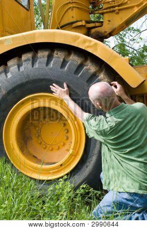 Man Checking Large Tire