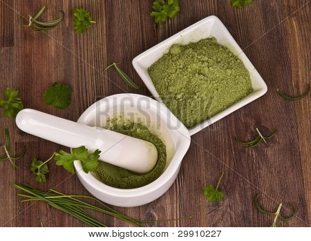 Mortar with herbs on wooden background