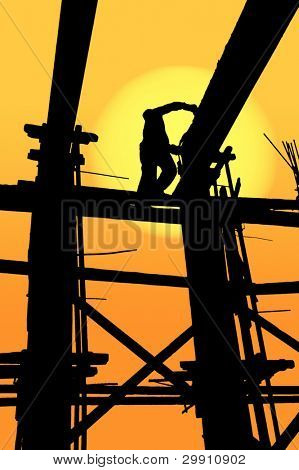 Construction worker on site at sunset; silhouetted scene