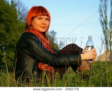 Young Girl Drinks Water On A Background Of The Sky