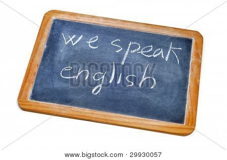 sentence we speak english written with chalk on a blackboard