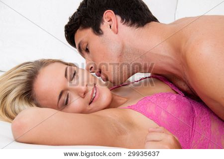 couple in bed during sex and tenderness. love and eroticism in the bedroom.