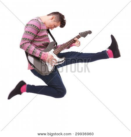 passionate guitarist jumps in the air on white background. casual man playing an electric guitar and jumping