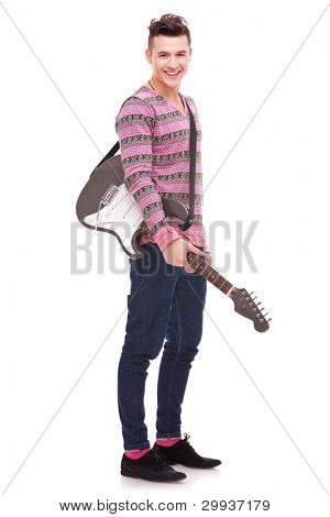 Rock star with an electric guitar isolated over white background . rock and roll image of a casual young man with a guitar on his shoulder, smiling to the camera
