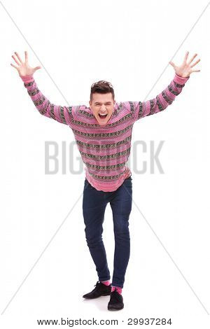 Casual man looking very happy with his arms up, isolated on white background . Excited young guy with hands in the air