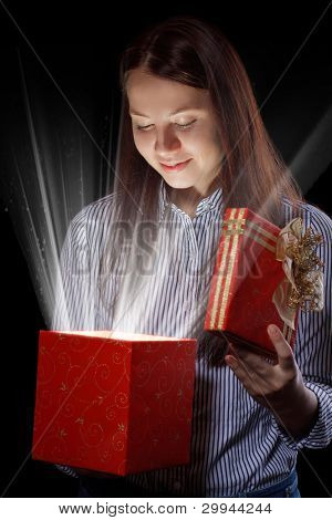 beautifull girl opening gift box. Black background