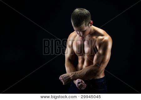 Artistic shot of a young man holding his hands as if being cuffed, dark background