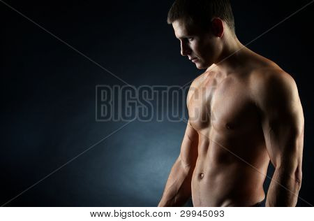 A portrait of a hot guy man without a shirt against dark background with copyspace